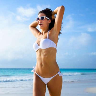 Beautiful joyful woman in white bikini enjoying tropical beach and caribbean summer vacation. Tanned brunette running free by the sea at Playa Paraiso, Riviera Maya, Mexico.