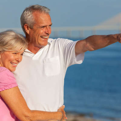 Happy senior man and woman couple walking and embracing on a deserted tropical beach with bright clear blue sky, the man pointing to the horizon